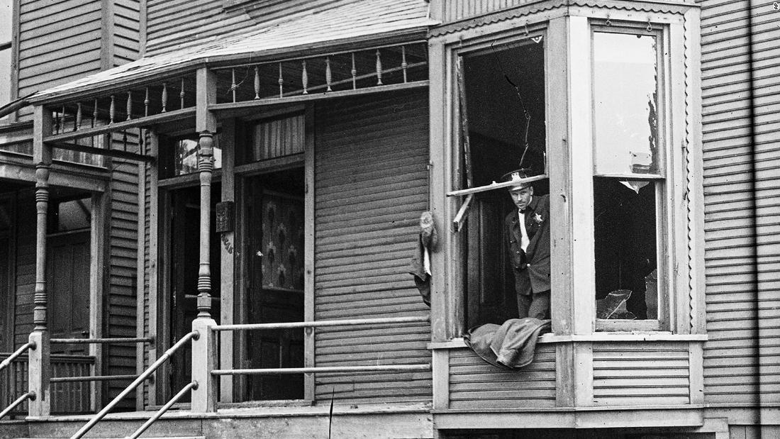 In this 1919 photo provided by the Chicago History Museum, police look through a broken window of a house during the race riots in Chicago. Broken furniture is strewn about the front yard. Hundreds of African Americans died at the hands of white mobs during Red Summer.