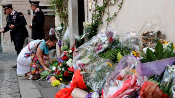 A woman leaves flowers in front of the police station where Mario Cerciello Rega was based in Rome, the day following his murder.