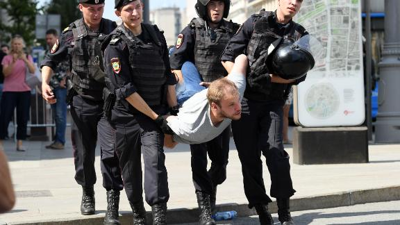 Police officers detain a man during an unauthorized rally demanding free and fair elections, outside the mayor's offices in Moscow on July 27, 2019.