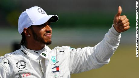 Lewis Hamilton of Great Britain and Mercedes GP waves to the crowd after securing pole position.