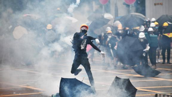 A protester throws tear gas back at police officers during a demonstration in the district of Yuen Long in Hong Kong on July 27, 2019.