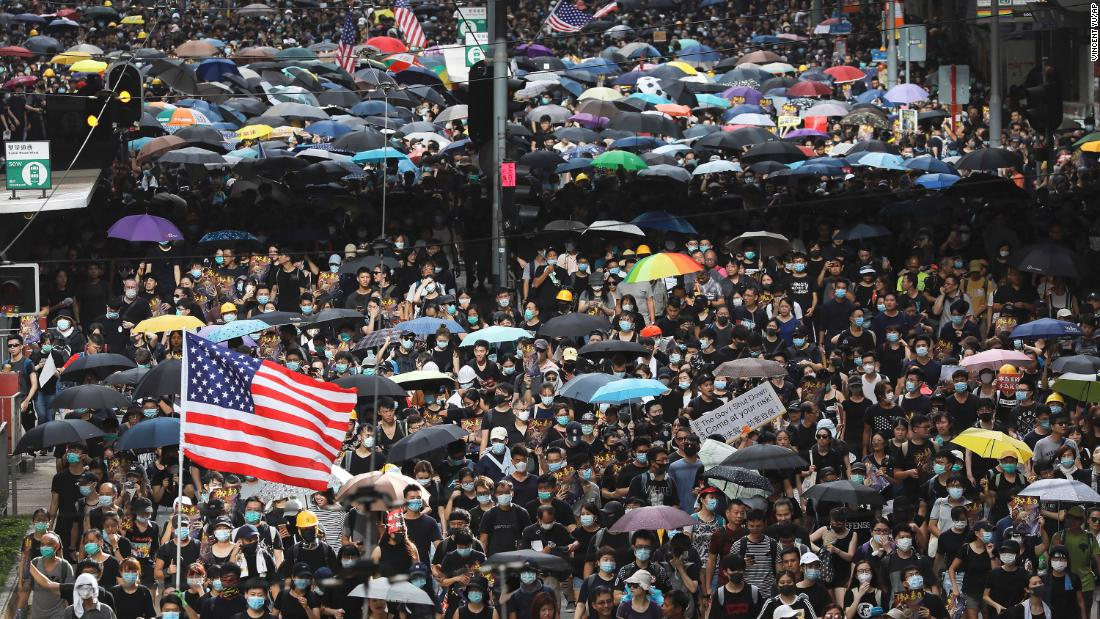Protesters carry US flags and placards during a march in Hong Kong on July 28.