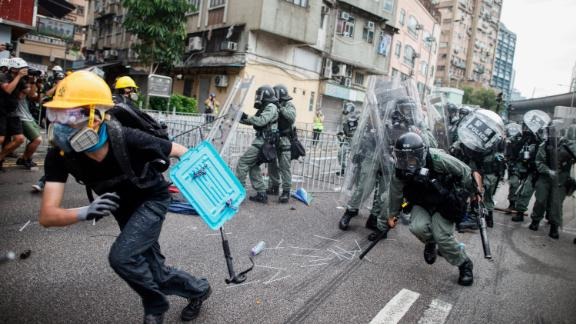 A protester flees from baton-wielding police in the Yuen Long district of Hong Kong on Saturday, July 27.