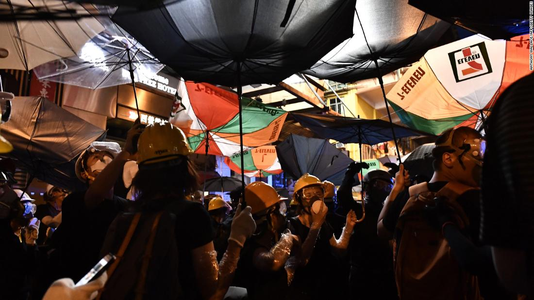 Protesters take shelter under umbrellas.