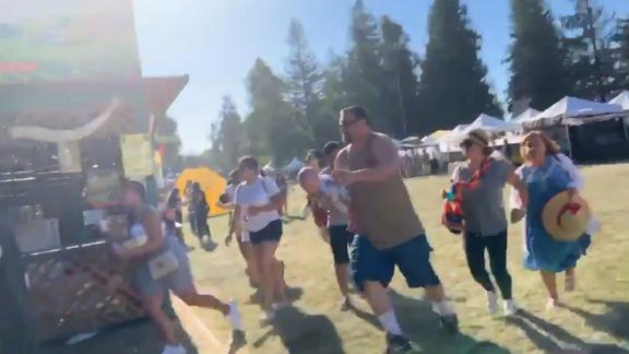 In this image, taken from a video posted on social media, people are seen running as an active shooter is reported at the festival.