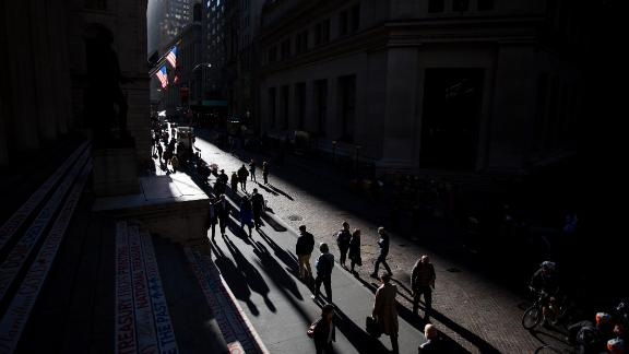 Pedestrians walk along Wall Street near the New York Stock Exchange (NYSE) in New York, U.S., on Monday, Oct. 31, 2016. U.S. stocks rose from a six-week low amid an increase in deal activity as traders assessed the outlook for the presidential election and interest rates in the world