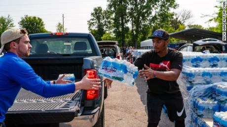 Flint, MI - JULY 25, 2019: Daevion Marshall, 19, works at Greater Holy Temple Church and delivers cases of water into the cars of residents every week. He throws a case of water to a med student volunteer from Indiana University, Chris Blanco, 24. CREDIT: Nick Hagen for CNN