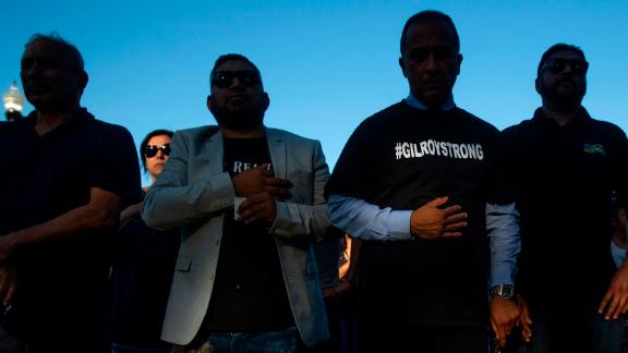 Gilroy City Council member Fred Tovar, center, wears a #GILROYSTRONG shirt while attending a vigil for victims of Sunday's deadly shooting at the Gilroy Garlic Festival on Monday, July 29, 2019, in Gilroy, Calif. (AP Photo/Noah Berger)