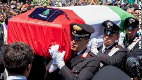 Rega's coffin was draped with the Italian flag. His funeral was attended by hundreds of mourners.