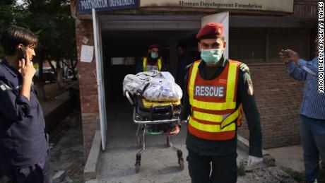 The body of a victim, killed after a Pakistani Army Aviation Corps aircraft crashed into residential buildings, is wheeled on a stretcher at hospital in Rawalpindi on July 30.