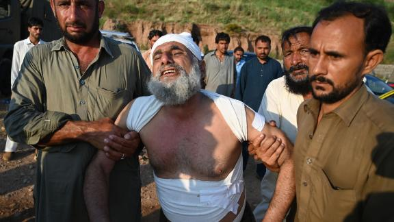 People assist a man at the scene where a Pakistani military aircraft crashed in Rawalpindi on July 30.