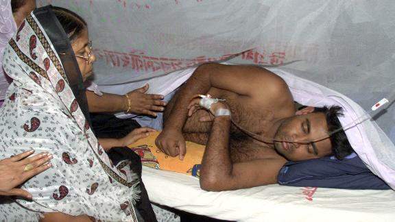 Relatives visit a victim of dengue fever at a hospital in Dhaka on August 20, 2002. REUTERS/Rafiqur Rahman