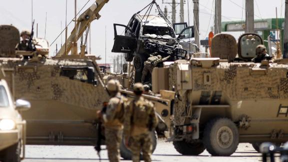 International forces belonging to NATO's Resolute Support mission remove a damage vehicle with a crane at the site of a car bomb attack in Kabul on May 31, 2019. - At least four Afghans were killed and four US troops lightly wounded when a car bomber attacked a US military convoy in Kabul on May 31, officials said. (Photo by STR / AFP/Getty Images)