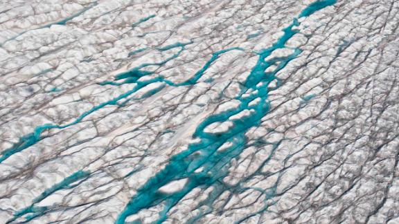 Melt water on the Greenland ice sheet. The Greenland ice sheet (Sermersuaq in Greenlandic) is a vast body of ice covering 1,710,000 square kilometers (660,000 sq mi), roughly 80% of the surface of Greenland. The thickness is generally more than 2 km (1.2 mi) and over 3 km (1.9 mi) at its thickest point. This section of the ice sheet was photographed on the Western part, close to Ilulissat and the glacier Semeq Kujalleq. Positioned in the Arctic, the Greenland ice sheet is especially vulnerable to climate change. (Photo by: Education Images/Universal Images Group via Getty Images)