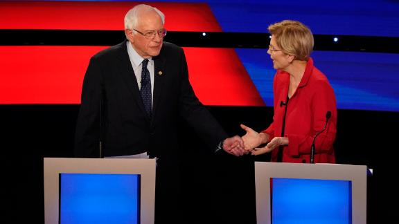 Sanders grabs the hand of US Sen. Elizabeth Warren during the Democratic debates in Detroit in July 2019.