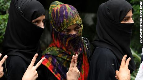 "Muslim women pose with a gesture as they celebrate the passage of a law to outlaw Triple Talaq, or ""instant divorce,"" at an event organised by the ruling Bharatiya Janata Party in New Delhi on July 31, 2019."