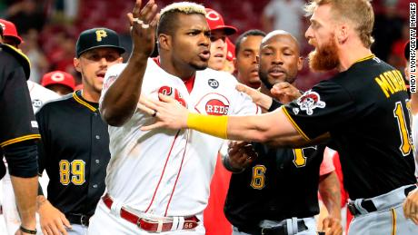 Yasiel Puig is restrained during a bench-clearing altercation in the ninth inning between the Reds and Pirates on Tuesday in Cincinnati.