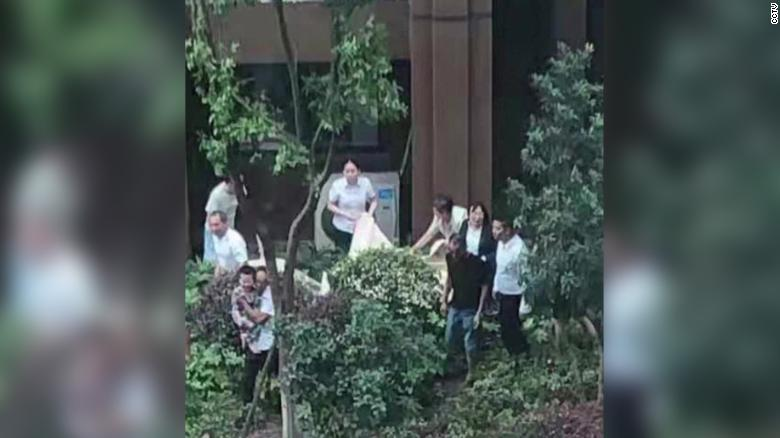 The 3-year-old boy was caught by a blanket, held by spectators below the building.