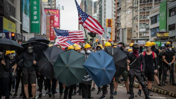 Protesters hold up umbrellas and American flags in the face of advancing riot police in the district of Yuen Long on July 27.