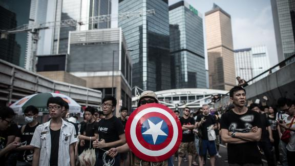 """Pro-democracy protesters, including one carrying a shield from the """"Captain America"""" comic book series stand their ground during protests in Hong Kong on October 4, 2014."""