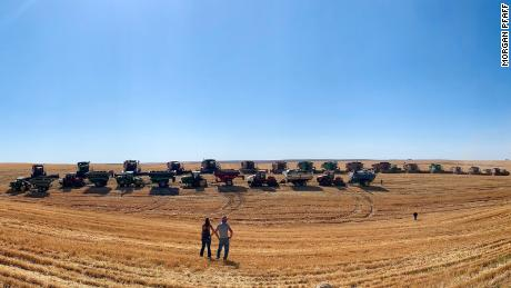 Farmer Larry Yockey and his daughter look out on his field as fellow farmers harvest his wheat.