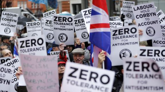 TOPSHOT - People hold up placards and Union flags as they gather for a demonstration organised by the Campaign Against Anti-Semitism outside the head office of the British opposition Labour Party in central London on April 8, 2018. - Labour leader Jeremy Corbyn has been under increasing pressure to address multiple allegations of anti-Semitism within the party, which saw protesters gather outside the party's head office in London after Jewish campaigners demonstrated outside parliament two weeks ago. (Photo by Tolga AKMEN / AFP)        (Photo credit should read TOLGA AKMEN/AFP/Getty Images)