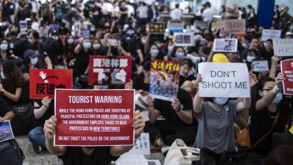 Demonstrators hold placards in the arrival hall during a protest at the Hong Kong International Airport in Hong Kong, China, on Friday, July 26, 2019. Hundreds of protesters staged a sit-in at Hong Kongs main international airport terminal on Friday, the first of three straight days of demonstrations after clashes last week triggered fears that a wider confrontation could erupt in the Asian financial hub. Photographer: Justin Chin/Bloomberg via Getty Images