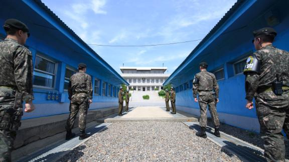 TOPSHOT - South Korean soldiers (front) and North Korean soldiers (rear) stand guard before the military demarcation line on the each side of the truce village of Panmunjom in the Demilitarized zone (DMZ) dividing the two Koreas on April 26, 2018 ahead of the inter-Korea summit. (Photo by - / Korea Summit Press Pool / AFP)        (Photo credit should read -/AFP/Getty Images)