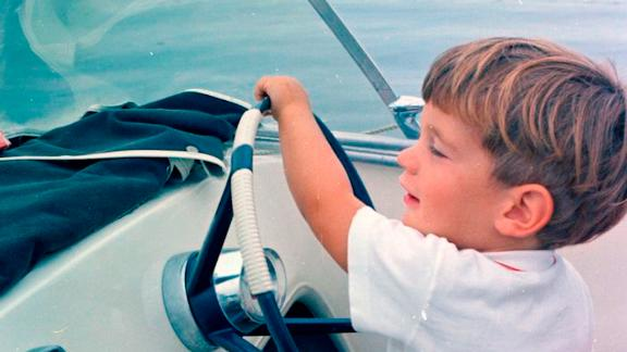John Jr. takes the wheel of a speedboat during Labor Day weekend in 1963.