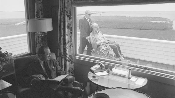 A man in Hyannis Port glances outside a window to see Joseph Sr. being pushed in a wheelchair in 1964. Joseph Sr., a former US ambassador to the United Kingdom, died in 1969.