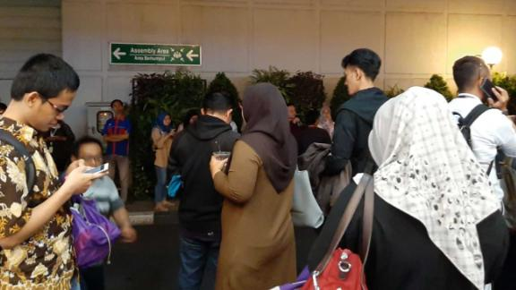 People stand outside after being evacuated following a strong earthquake in the area in Serpong, Banten province.