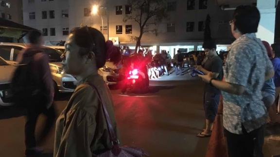 Residents stand outside an apartment block after a strong earthquake hit the area around Jakarta.