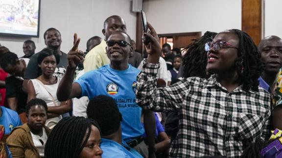 The overflowing courtroom sang Uganda's national anthem while they waited for the magistrate to arrive.