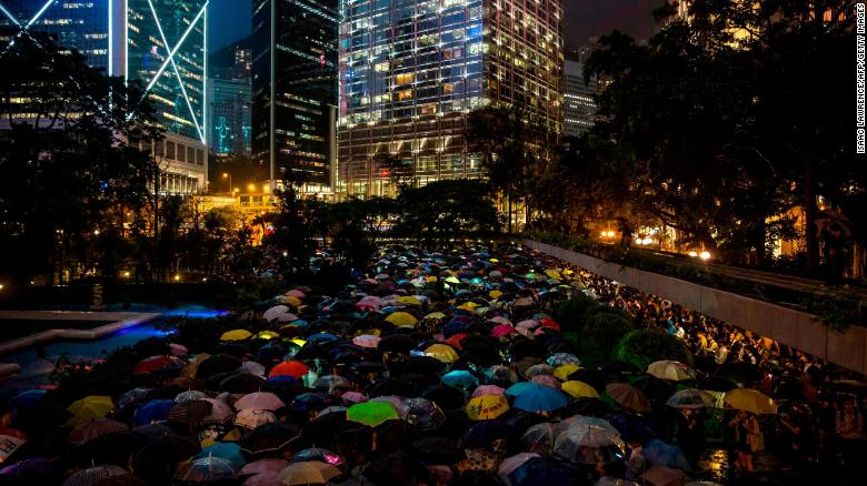 People from the finance community hold up umbrellas and shine lights during a protest against a controversial extradition bill in Hong Kong on August 1.