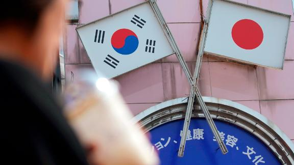 "A woman walks past an advertisement featuring Japanese and South Korean flags at a shop in Shin Okubo area in Tokyo Friday, Aug. 2, 2019. Japan has approved the removal of South Korea from a ""whitelist"" of countries with preferential trade status, escalating tensions between the neighbors. The decision will fuel antagonism between the two neighbors already at a boiling point over the export controls and the issue of compensation for wartime Korean laborers. (AP Photo/Eugene Hoshiko)"