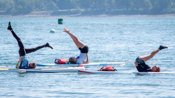 Paddleboard yoga, as seen here in a class in Maine, involves balancing on a paddleboard while doing yoga poses.