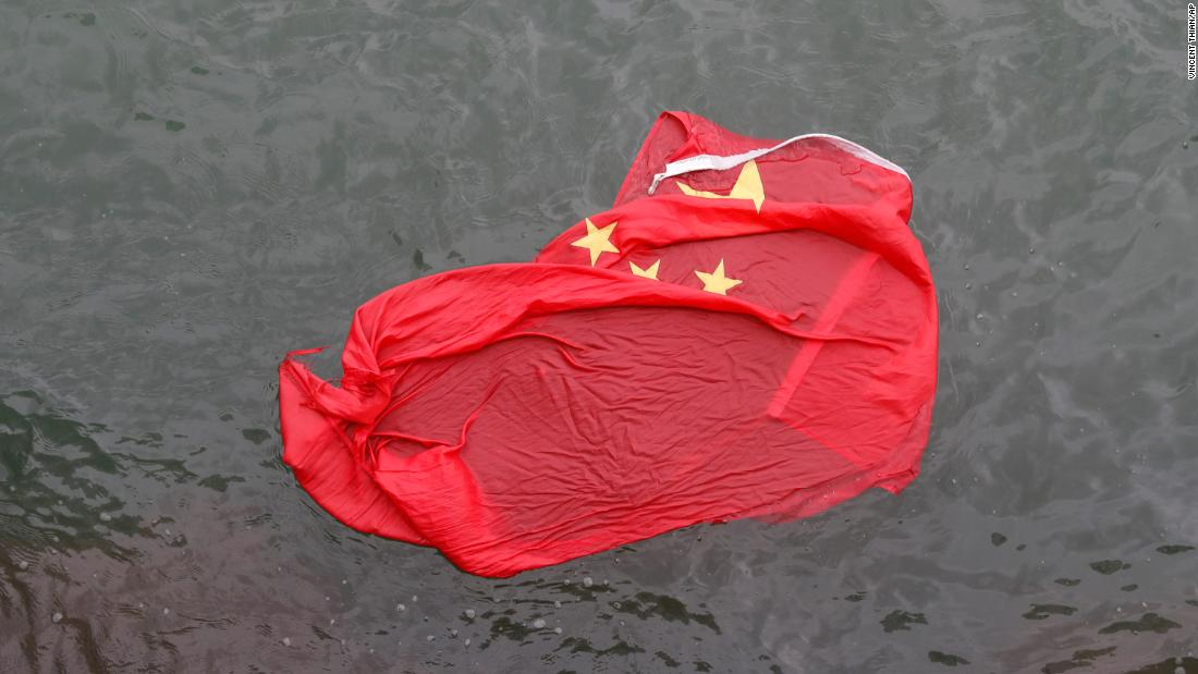 A Chinese flag floats in water after it was thrown by protesters during a demonstration on Saturday, August 3.