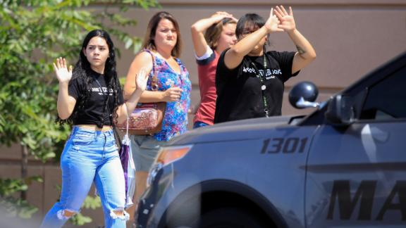 Shoppers exit the El Paso Walmart with their hands up.