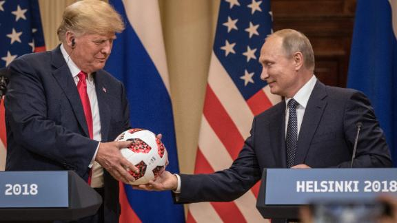 Putin hands Trump a World Cup soccer ball after their July 2018 summit in Helsinki, Finland.