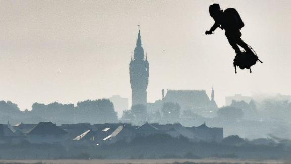 """Franky Zapata on his jet-powered """"flyboard"""" flies past the belfry of the city hall of Calais (C) after he took off from Sangatte, northern France, on August 4, 2019, during his attempt to fly across the 35-kilometre (22-mile) Channel crossing in 20 minutes, while keeping an average speed of 140 kilometres an hour (87 mph) at a height of 15-20 metres (50-65 feet) above the sea. - Frenchman who has spent years developing a jet-powered hoverboard will again try to zoom across the English Channel on August 4, after a first attempt last month was cut short when a botched refuelling attempt sent him into the water. (Photo by Denis Charlet / AFP)        (Photo credit should read DENIS CHARLET/AFP/Getty Images)"""