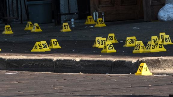 """Police mark evidence after an active shooter opened fire in the Oregon district in Dayton, Ohio on August 4, 2019. - Nine people were killed in a mass shooting early Sunday in Dayton, Ohio, police said, adding that the assailant was shot dead by responding officers.The incident occurred shortly after 1:00 am in the popular bar and nightlife Oregon district of the city, Police Lieutenant Colonel Matt Carper said.""""We had one shooter that we are aware of and multiple victims,"""" he told reporters.""""The shooter is deceased, from gunshot wounds from the responding officers,"""" he said, adding no police were injured.""""We have nine victims deceased ... and we have approximately 16 more victims hospitalized right now in unknown conditions.""""The suspect had opened fire on the street firing """"a long gun with multiple rounds."""" (Photo by Megan JELINGER / AFP)        (Photo credit should read MEGAN JELINGER/AFP/Getty Images)"""