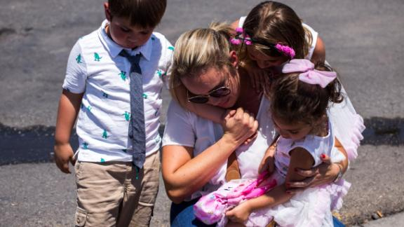 Cristina Zapata, 35, second from left, is comforted by her children David Burgos, 4, left, Lucy Burgos, 7, second from right, and Mariana Burgos, 3, right, as they pay their respects to the victims of the El Paso shooting at a memorial in a lot across from the Walmart near Cielo Vista Mall in El Paso, Texas, Sunday, Aug. 4, 2019.