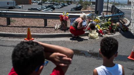 Jessica Windham, 35, top left, and her children Kalani Windham, 2, top right, Andre Newell, 8, bottom left, and Maxwell Windham 5, bottom right, pay their respects to the victims of the El Paso shooting at a memorial in a lot across from the Walmart near Cielo Vista Mall in El Paso, Texas, Sunday, Aug. 4, 2019.