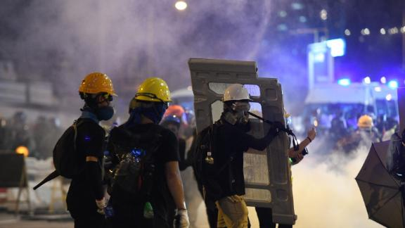 Protesters hold up makeshift defenses amid clouds of tear gas in Causeway Bay, Hong Kong, on August 4, 2019.