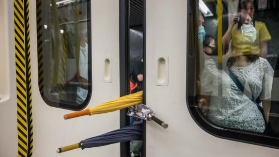 A group of protesters prevent the doors of a commuter train from closing on August 5.