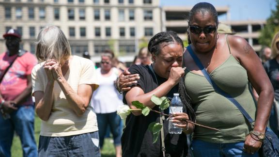 Mourners gather Sunday at a vigil in Dayton.