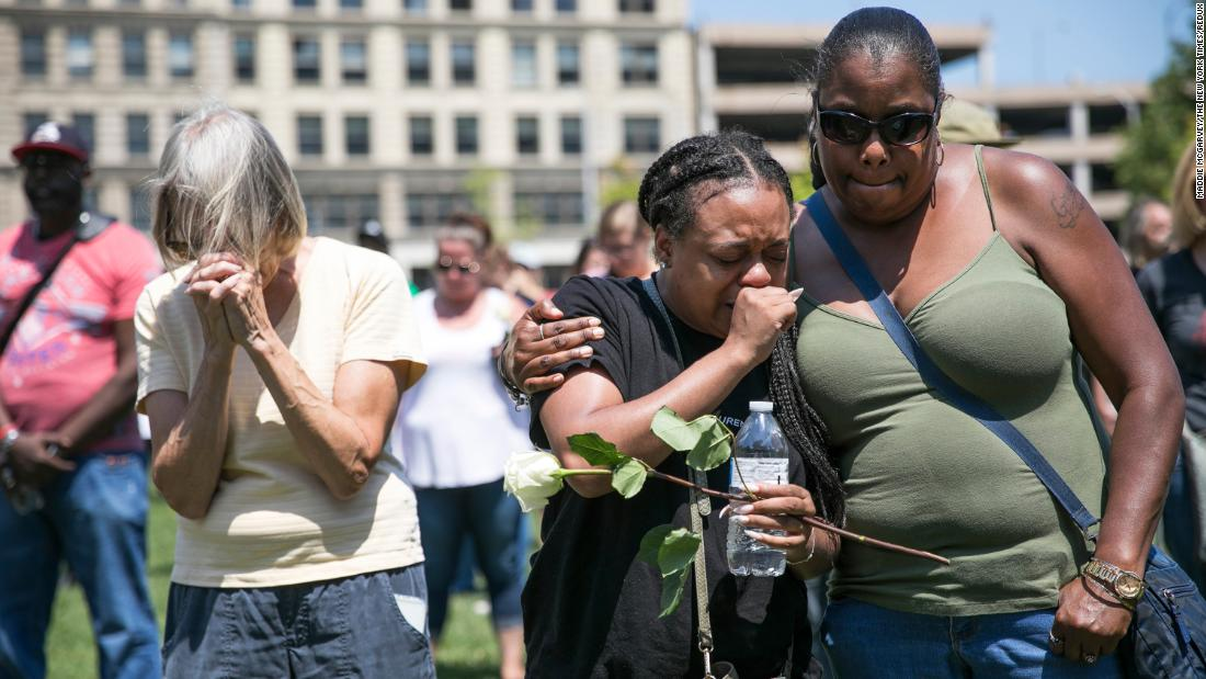 Mourners gather Sunday at a vigil in Dayton.