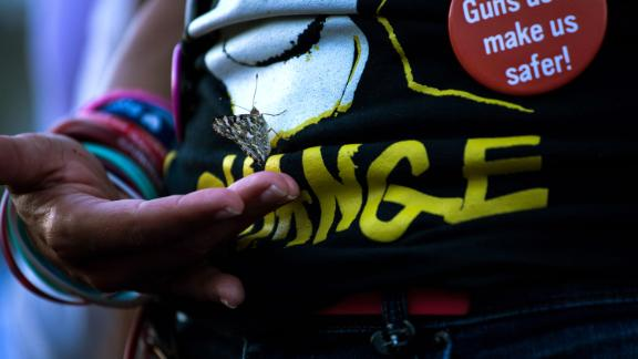 A butterfly grips onto Patricia Oliver during an El Paso vigil. Oliver's son, Joaquin, was killed in the Parkland, Florida, school shooting in 2018. Sunday would have been his 19th birthday.