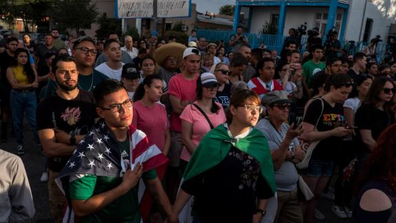 """Cesar Antonio Pacheco, 24, left, and Samantha Ordaz, 20, both of El Paso, hold hands during a vigil, for the victims of the Aug. 3 deadly mass shooting in El Paso, outside Las Americas Immigrant Advocacy Center in El Paso, Texas, Sunday, Aug. 4, 2019. """"Above all,"""" said Ordaz, """"we need to love each other equally because love covers a multitude of hatred."""""""
