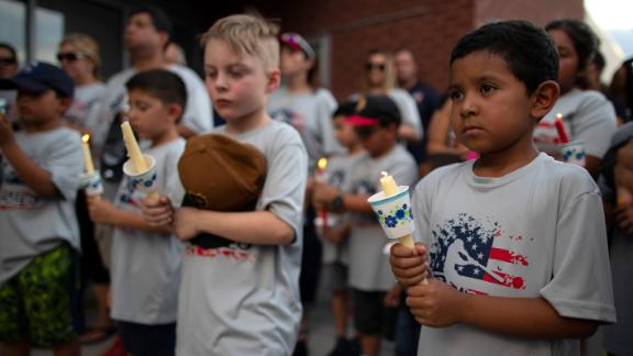 Children of a youth sports community participate in a vigil for the victims of Saturday